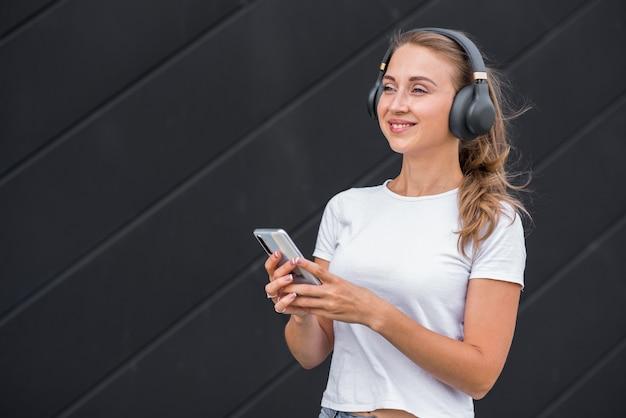Feliz e atraente loira caucasiana usando um smartphone e ouvindo música em fones de ouvido.