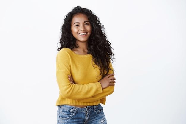 Feliz e atraente mulher afro-americana de braços cruzados e rindo confiante, olhando para a câmera com um sorriso alegre e encantador, usar um suéter amarelo sobre a parede branca, conceito de bem-estar