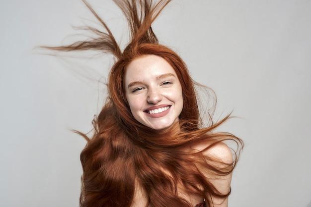Feliz e bela jovem alegre com cabelo ruivo despenteado, olhando para a câmera e sorrindo em pé contra um fundo cinza