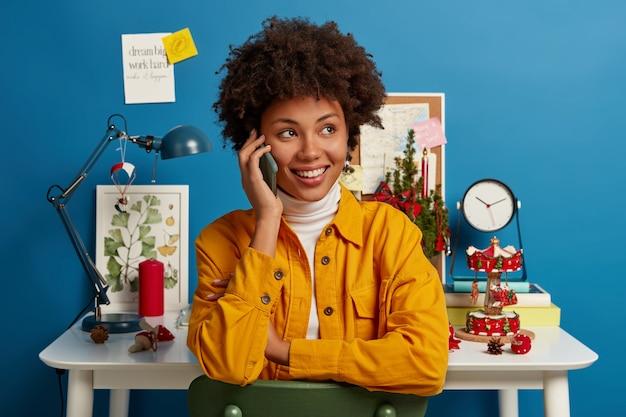 Feliz e bem-sucedida empresária afro-americana conversa por telefone, discute planos com um colega via smartphone, trabalha como freelance em casa, desvia o olhar com um sorriso, posa perto de uma área de trabalho interna