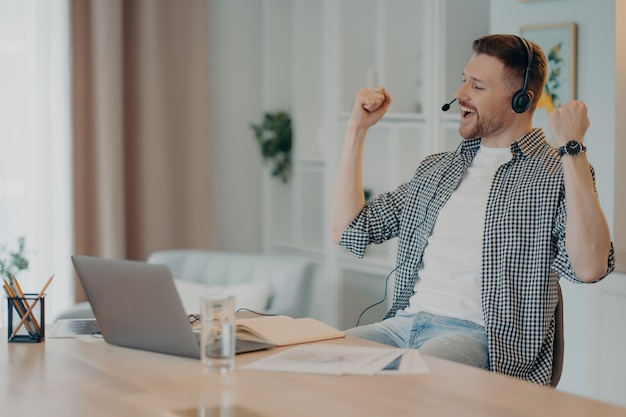 Feliz e bem-sucedido homem cerrou os punhos celebra o triunfo trabalha online usa poses de fone de ouvido na área de trabalho com o computador laptop vestido casualmente. aluno muito feliz ouve palestra educacional online