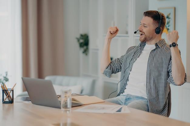 Feliz e bem sucedido homem cerrou os punhos celebra o triunfo trabalha online usa poses de fone de ouvido na área de trabalho com o laptop vestido casualmente aluno muito feliz ouve palestra educacional online
