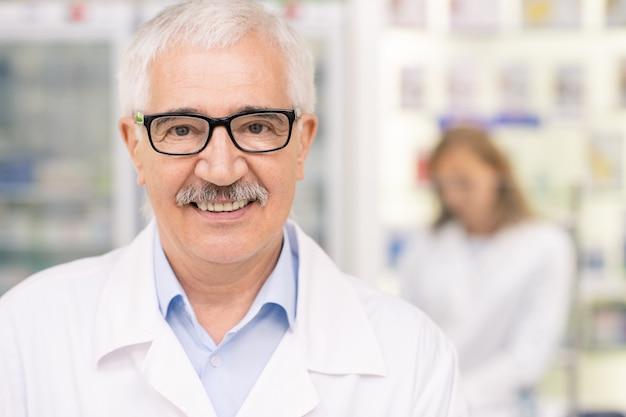 Feliz e bem sucedido profissional sênior de óculos e jaleco em pé na frente da câmera na farmácia no fundo do jovem farmacêutico