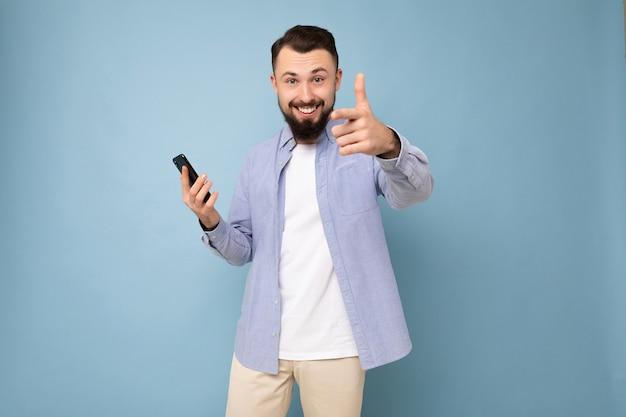 Feliz e bonito jovem moreno com barba por fazer e barba usando uma elegante camiseta branca e uma camisa azul