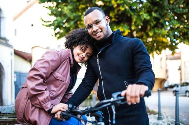 Feliz e contente casal étnico negro sentado na bicicleta. Foto Premium