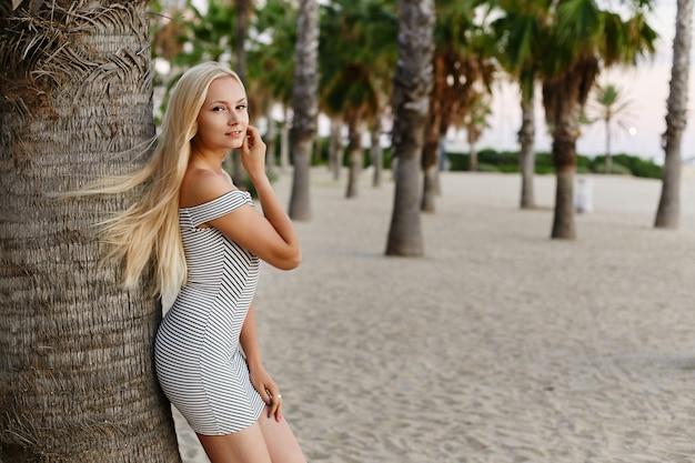 Feliz e elegante garota loira modelo com corpo sexy em um vestido curto listrado da moda magra no amigo ...