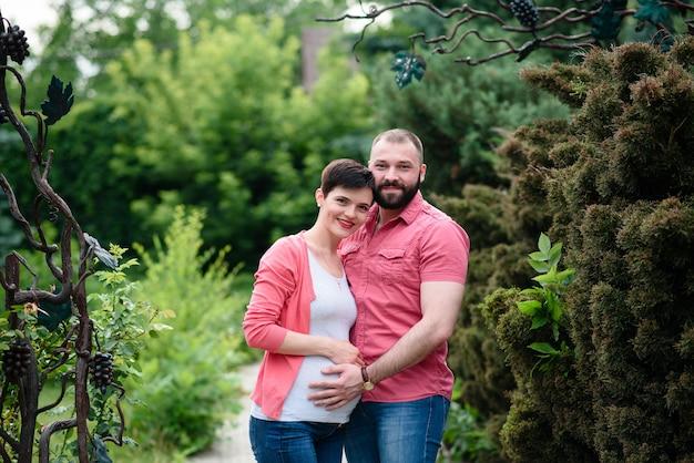 Feliz e jovem casal grávida abraçando na natureza