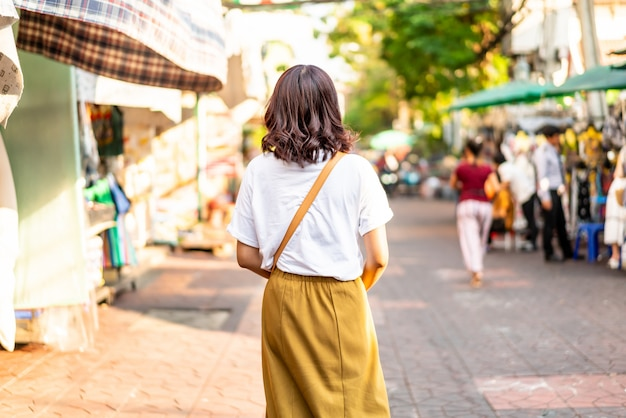 Feliz e linda mulher asiática viajando na khao sarn road, tailândia