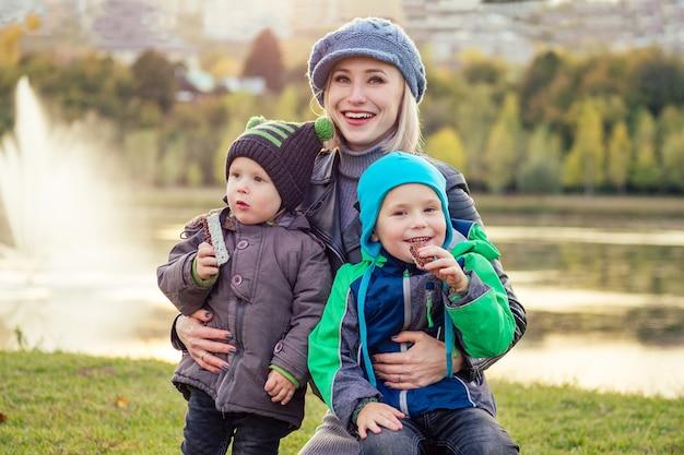 Feliz e linda mulher loira com chapéu com dois filhos, comendo uma barra de chocolate em uma jaqueta quente no parque outono, contra o pano de fundo do lago. mãe estilosa com criança lanche saboroso piquenique