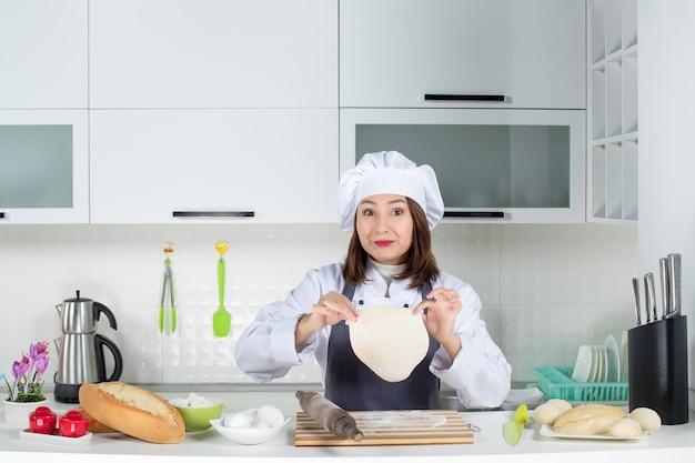 Feliz e positiva, chef feminina de uniforme, em pé atrás da mesa, preparando a massa na cozinha branca