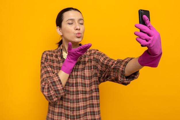Feliz e positiva, jovem faxineira com camisa xadrez e luvas de borracha segurando um smartphone, fazendo selfie, mandando um beijo em pé sobre uma parede laranja