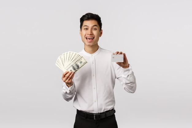 Feliz e rico, bem sucedido rapaz asiático com roupa formal, segurando dinheiro e cartão de crédito, rindo e sorrindo, se gabando de estabilidade financeira, tem duas variantes de pagamento, escolhendo o banco