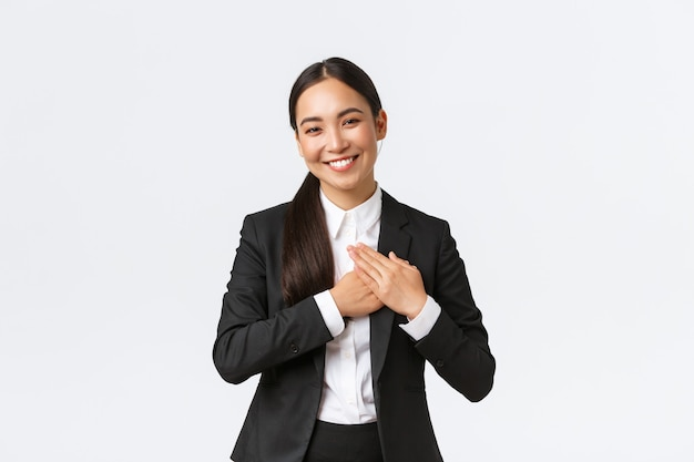 Feliz e satisfeita empreendedora asiática ama seus clientes, sentindo-se lisonjeada ao receber elogios com ótimo trabalho, segurando o coração de mãos dadas e sorrindo agradecida, sendo grata e apreciando os esforços