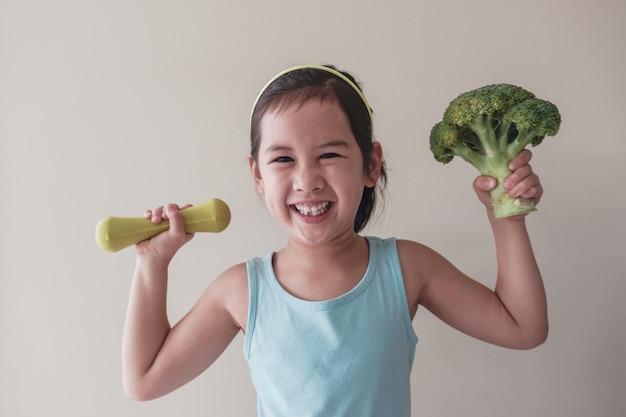 Feliz e saudável menina misturada levantando um brócolis e um haltere, conceito de bem-estar de criança