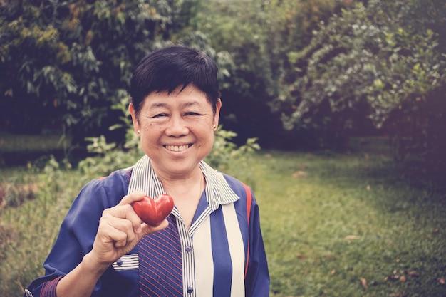 Feliz e saudável mulher sênior asiática segurando coração vermelho em um jardim