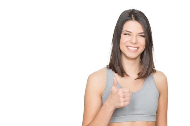Feliz e saudável. retrato de uma mulher atraente em roupas esportivas aparecendo os polegares isolados no branco