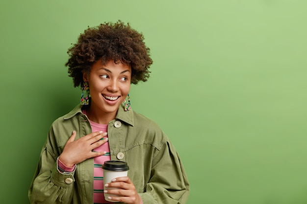 Feliz e sincera senhora afro-americana concentrada positivamente ao lado de sorrisos amplamente vestidos com roupas elegantes bebidas café para viagem isolado sobre uma parede verde vibrante