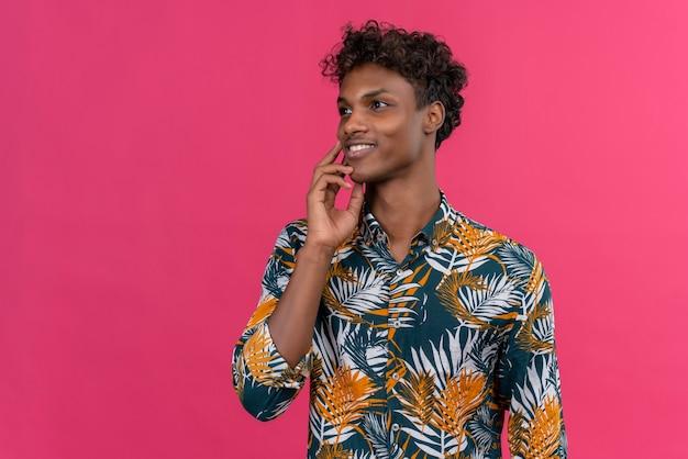 Feliz e sorridente jovem bonito de pele escura com cabelo encaracolado em uma camisa estampada de folhas mantendo a mão no queixo e olhando para longe em um fundo rosa