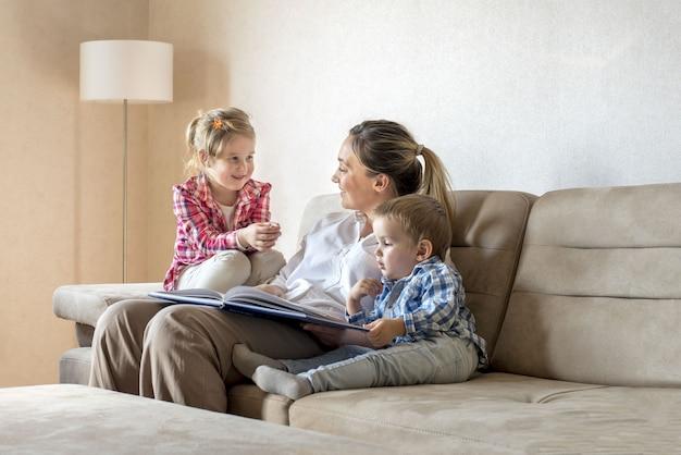 Feliz e sorridente mãe caucasiana com filhos lendo um livro e se divertindo em casa