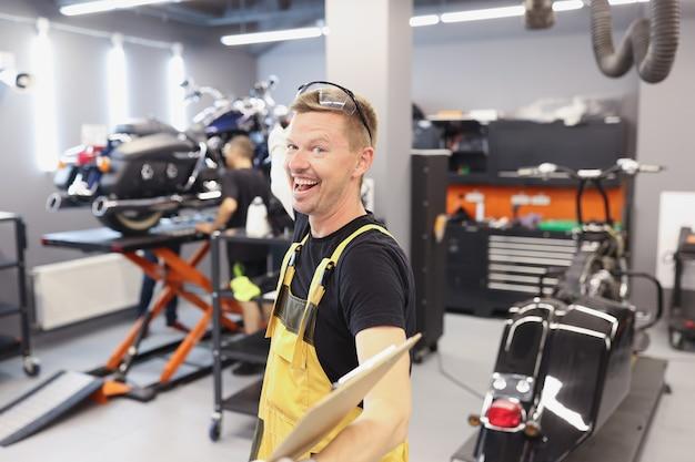 Feliz e sorridente mecânico de automóveis ou chaveiro com prancheta no serviço e manutenção do carro da oficina