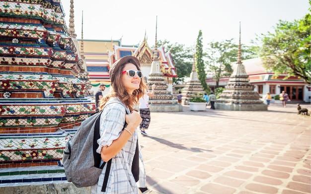 Feliz e sorridente mulher europeia linda jovem de chapéu e óculos em um templo budista em bangkok