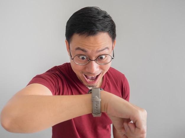 Feliz e surpreso homem asiático que está olhando para o relógio dele.