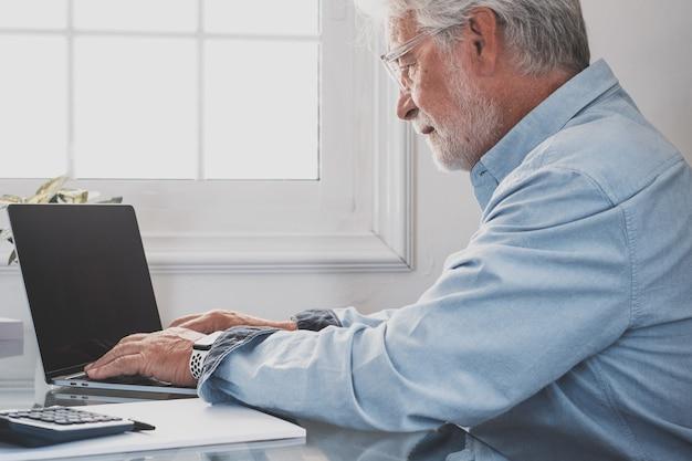Feliz e velho empresário caucasiano sorrindo, trabalhando on-line, assistindo ao podcast do webinar no laptop e fazendo chamadas em conferência do curso de educação de aprendizagem, faça anotações, sente-se na mesa de trabalho, conceito de elearning