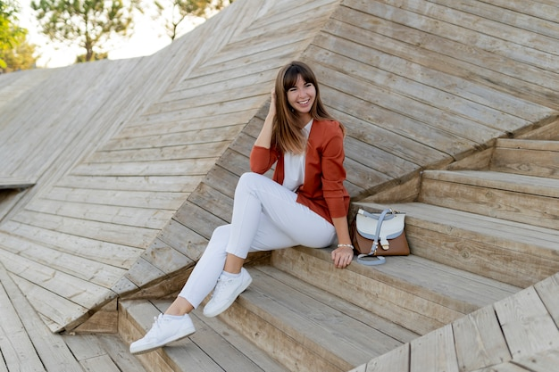 Feliz elegante aluna posando no parque moderno, vestindo jeans branco, jaqueta e camiseta.