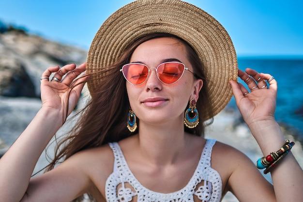Feliz elegante mulher morena bonita com os olhos fechados, vestindo um chapéu de palha, brincos grandes e óculos vermelhos, aproveitando o verão