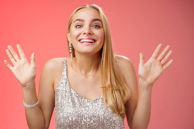 Feliz, elegante, sonhadora, glamour, jovem, mulher loira, levantando as mãos, sorrindo alegremente para a câmera, feliz por ver amigos chegando na festa dando as boas-vindas aos convidados sorrindo alegremente, usando um vestido prateado elegante
