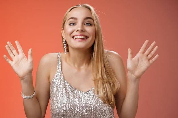 Feliz elegante sonhadora glamour loira jovem levantando as mãos deliciosamente sorrindo câmera feliz em ver amigos chegando na festa dando as boas-vindas aos convidados sorrindo alegremente, usando um vestido prateado elegante.