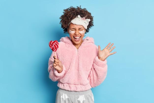 Feliz emocional jovem garota afro-americana exclama de alegria, levanta palma reage a notícias incríveis, vestida de pijama segura bala doce no palito isolado sobre a parede azul