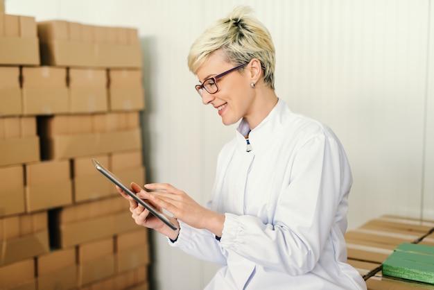 Feliz empregado loiro caucasiano processando tablet para o trabalho enquanto está sentado em torno de caixas na fábrica de alimentos.