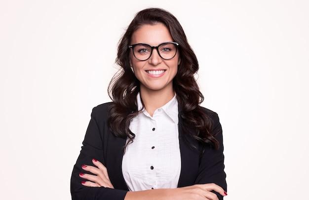 Feliz empresária adulta bem-sucedida em roupa formal e óculos elegantes, sorrindo e olhando em pé com os braços cruzados