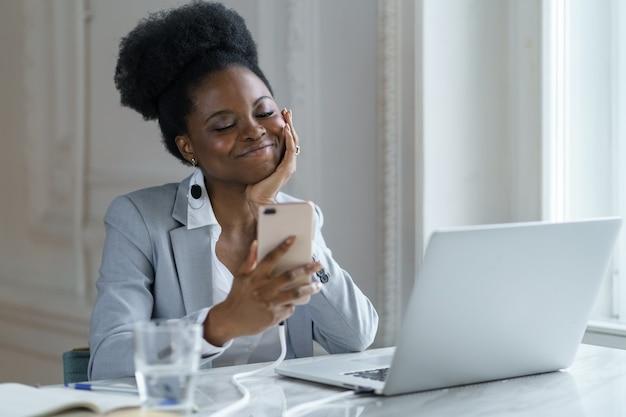 Feliz empresária africana olha para o telefone inteligente trabalhando no laptop no escritório com um sorriso fofo