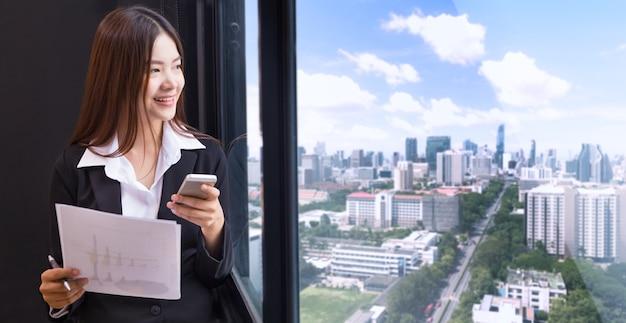 Feliz empresária asiática atraente no terno de pé em seu escritório olhando pela janela