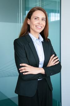 Feliz empresária bem-sucedida, ruiva, vestindo terno formal, de pé com os braços cruzados e sorrindo