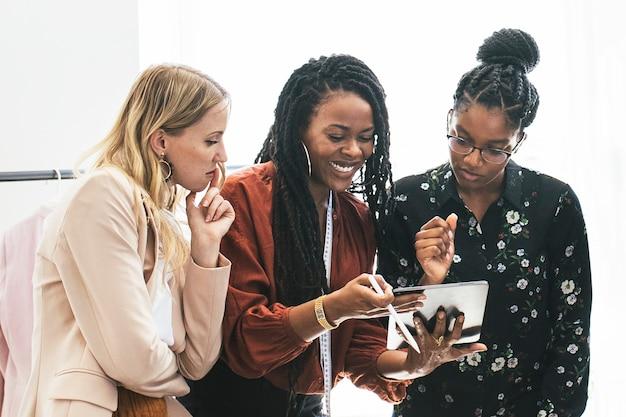 Feliz empresária diversa usando um tablet digital