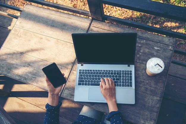 Feliz empresária empresária usando smartphone e laptop