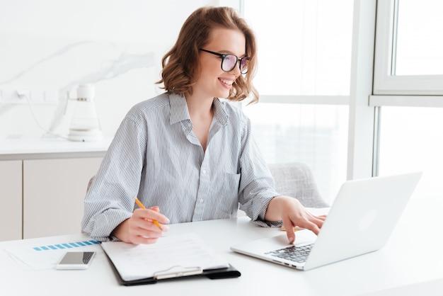 Feliz empresária morena em copos usando computador portátil enquanto trabalhava no apartamento de luz