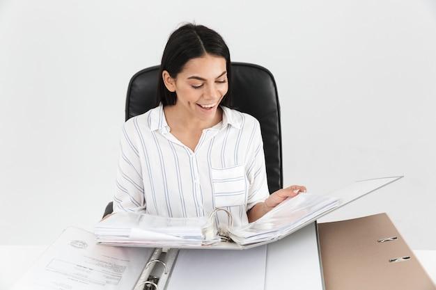 Feliz empresária morena trabalhando e sentada no escritório com um monte de pastas de papel na mesa isolada sobre a parede branca