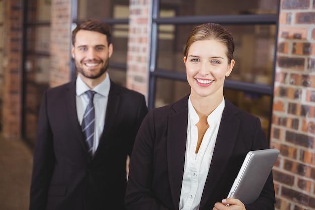 Feliz empresária permanente com colega masculina