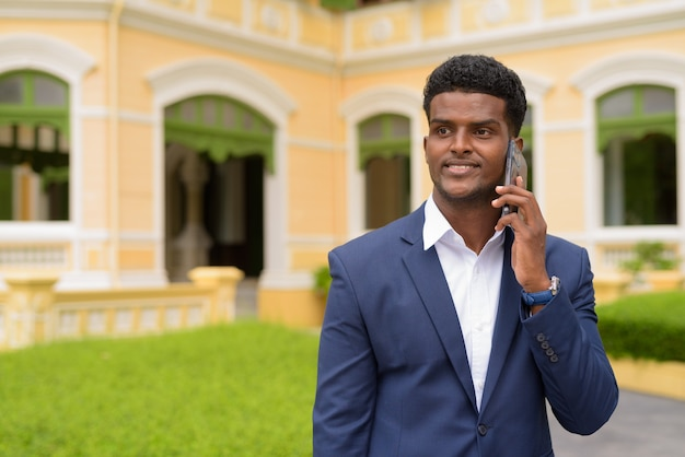 Feliz empresário africano ao ar livre, vestindo terno e falando no celular enquanto sorri, tiro horizontal