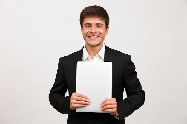 Feliz empresário alegre em pé isolado segurando o computador portátil.