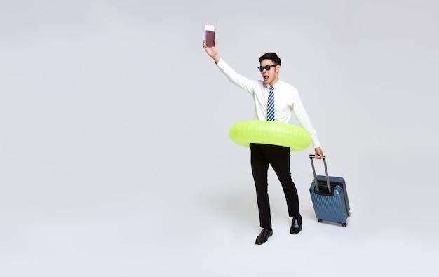 Feliz empresário asiático com passaporte e bagagem, aproveitando sua escapadela de férias de verão.
