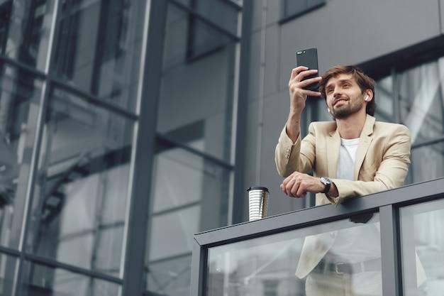 Feliz empresário barbudo de terno e smartphone sem fio tendo videoconferência no smartphone ao ar livre
