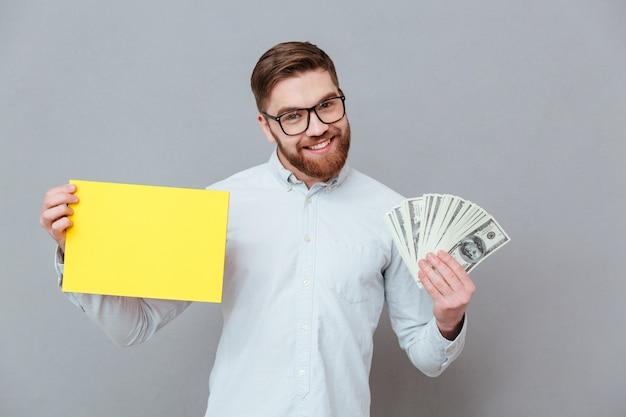 Feliz empresário barbudo segurando copyspace em branco e dinheiro