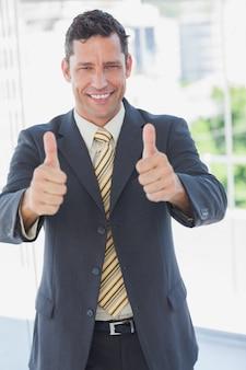 Feliz empresário com polegares para cima
