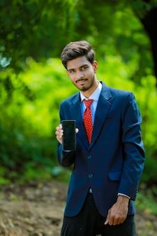 Feliz empresário com smartphone ao ar livre