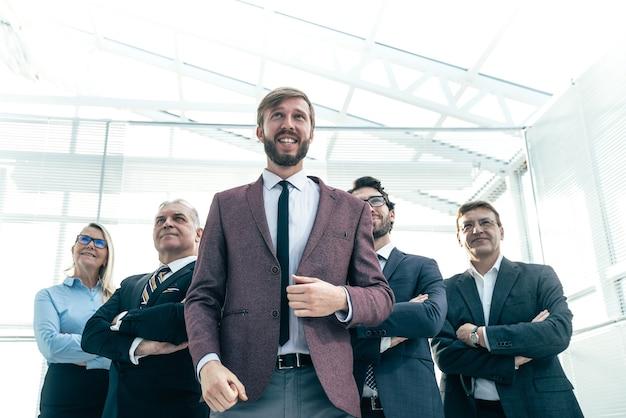 Feliz empresário com sua equipe de negócios em pé no escritório. conceito de sucesso
